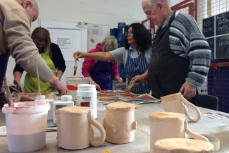 Group making and decorating clay items in Letchworth
